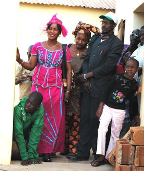 Skole Tiéba Bs lærere og skoleinspektør i lyserødt følger spændt med, da deres elever er på scenen