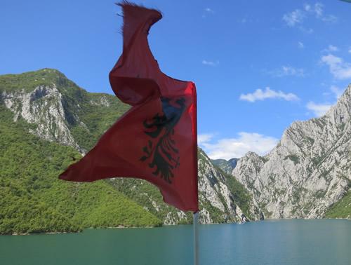 Det albanske flag ser ekstra godt ud, som kontrastfarve til det turkise vand, den blå himmel og de grønne bjergsider.